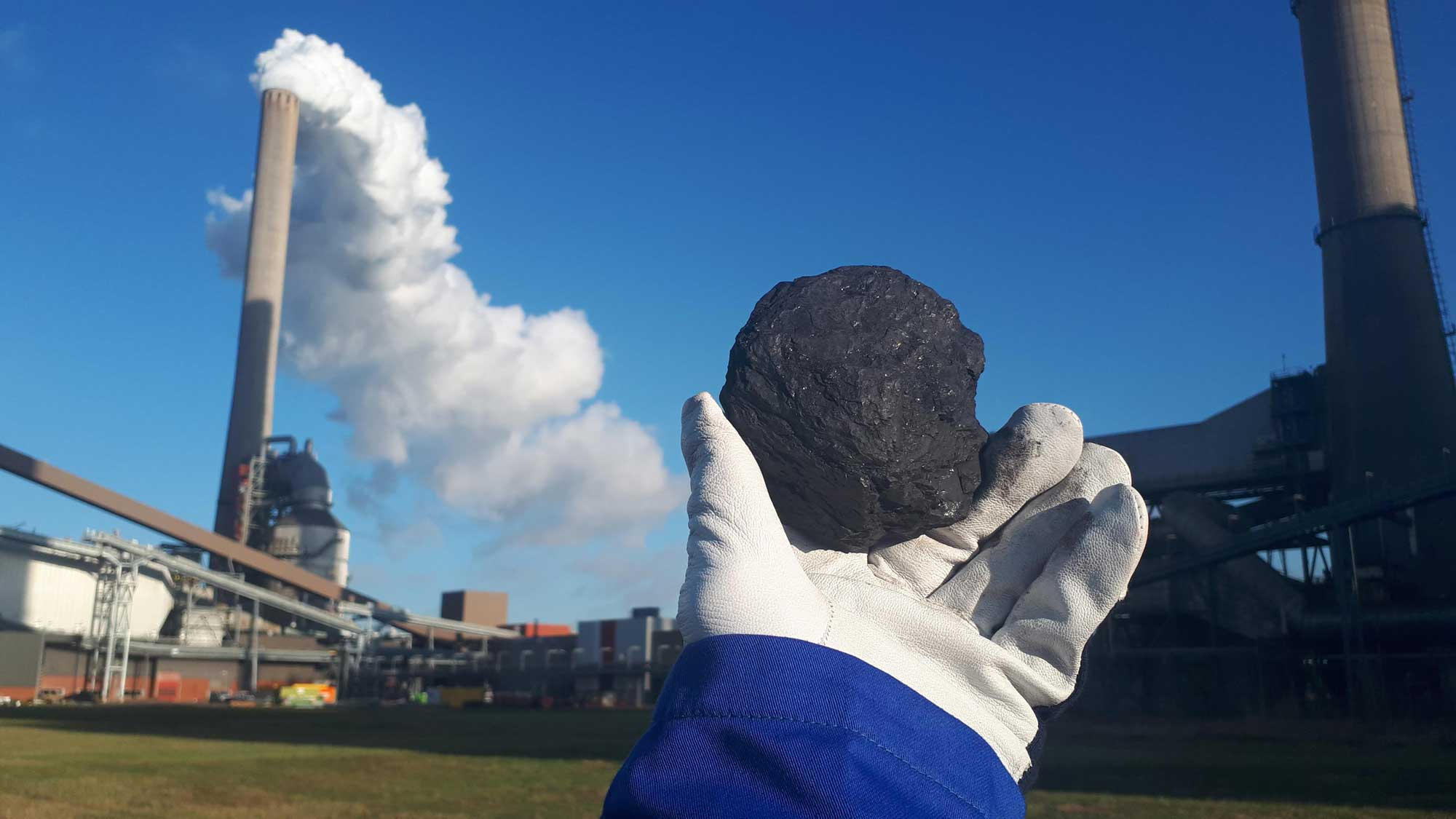 Photograph of a person holding a chunk of coal in front of a power plant.