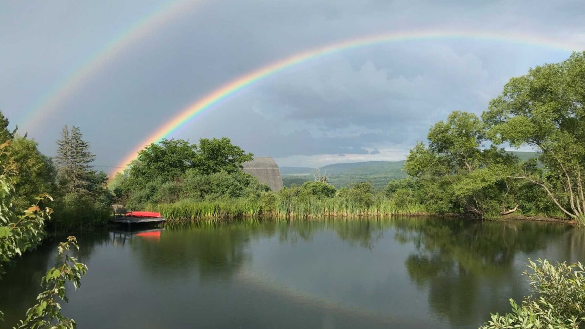 Photograph of a double rainbow over a pond.