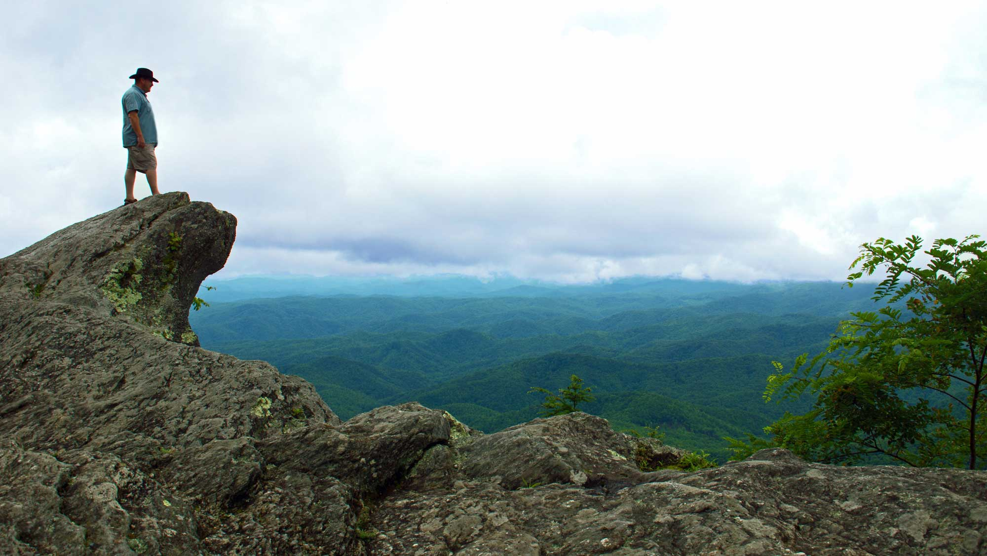Photograph of a man standing on the Blowing Rock.