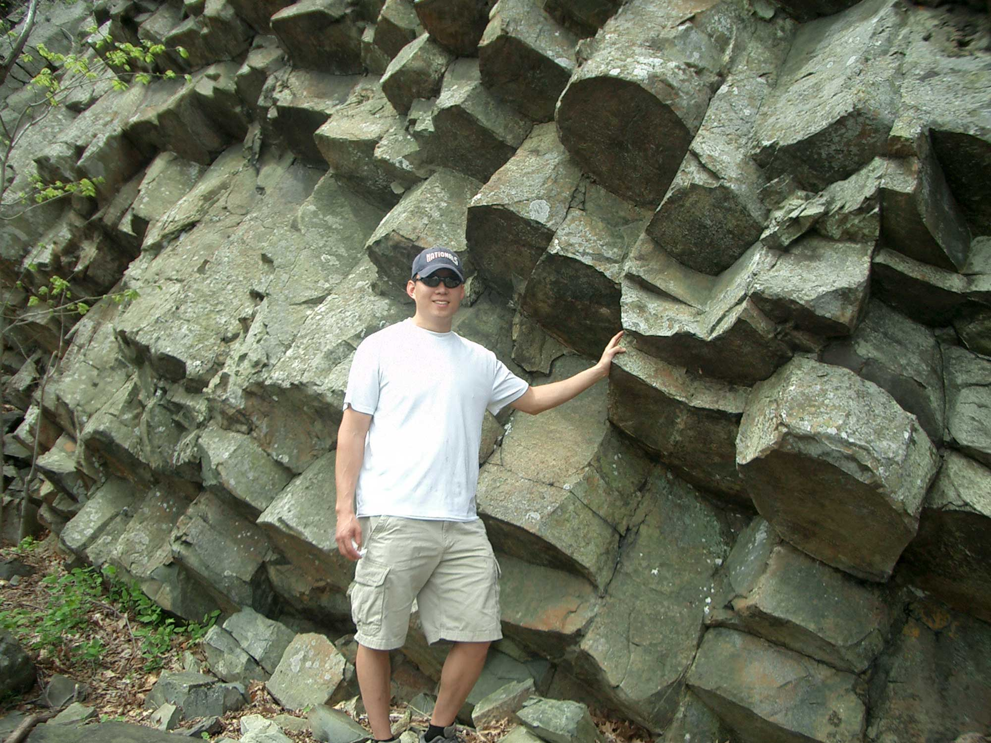 Photograph of a man standing next to greenstone rocks that exhibit columnar jointing.