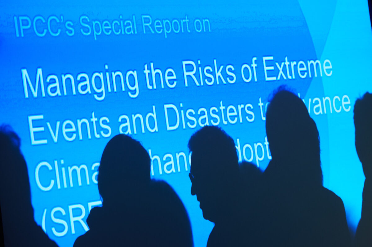 Image of a screen showing an IPCC report, and silhouettes of people in front of it.